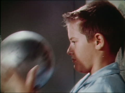 vidéos et rushes de 1962 close up side view of boy letting go of steel ball on chain / flinching and laughing - attitude