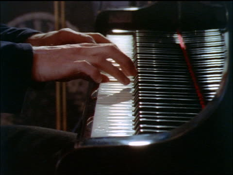 close up side view of hands of man playing piano