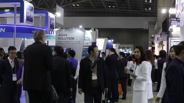 Close up signage for the Automotive World 2018 forum is displayed in Tokyo Japan on Wednesday Jan 17 Attendees walk past booths at the Automotive...
