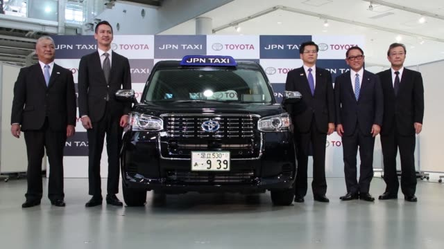 Close up signage for Toyota Motor Corp's JPN Taxi is displayed on the vehicle during its launch in Tokyo Japan on Monday Oct 23 Ribbons hang in front...