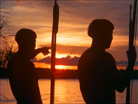 stockvideo's en b-roll-footage met close up silhouette of 2 native men pointing in distance / amazonas, brazil - latijns amerikaanse cultuur