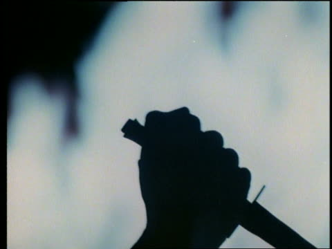 close up silhouette of hand raising a dagger