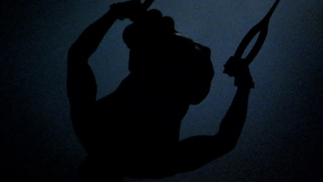 close up silhouette of male gymnast performing routine on rings - sagoma controluce video stock e b–roll