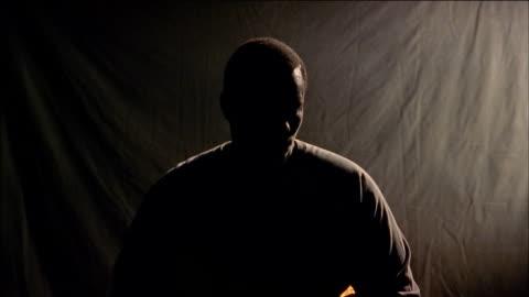 close up silhouetted black man turning head - silhuett bildbanksvideor och videomaterial från bakom kulisserna