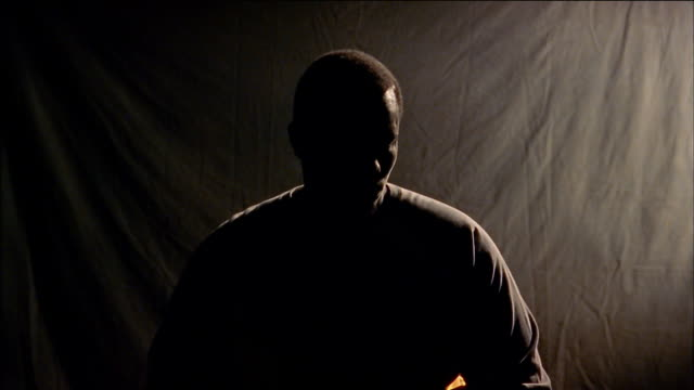 close up silhouetted black man turning head - freisteller neutraler hintergrund stock-videos und b-roll-filmmaterial