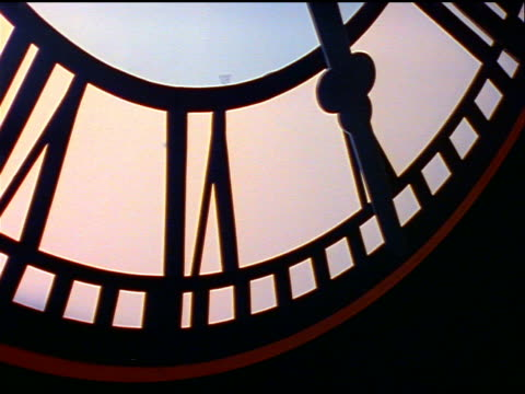 close up silhouetted clock hand moving - inquadratura dall'alto di un tavolo video stock e b–roll