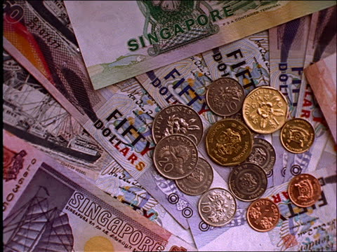 close up pan of singapore money (bills + coins) - anno 1997 video stock e b–roll