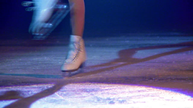 close up skates of female figure skater spinning on ice faster + faster