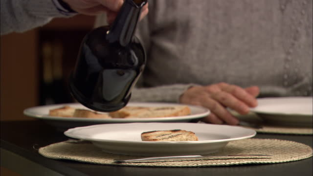 Close up slice of grilled bread (bruschetta) on plate / zoom out senior man pouring olive oil on his and his wife's plate
