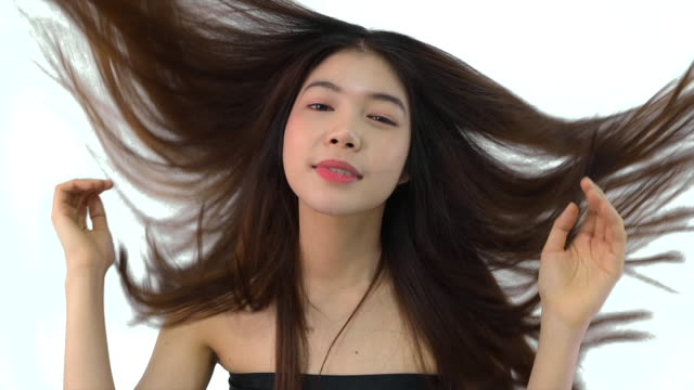 close up slow motion beauty shot of beautiful asian girl looking at camera isolated on white background - black hair stock videos & royalty-free footage