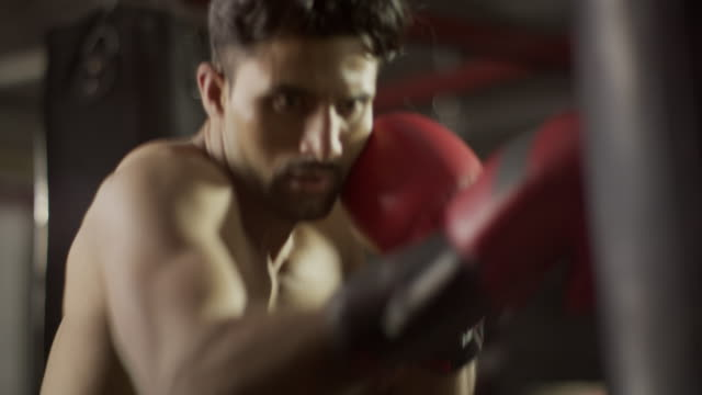 close up slow motion low angle panning shot of boxer hitting heavy bag / lehi, utah, united states - lehi stock videos & royalty-free footage