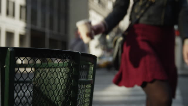 vídeos de stock, filmes e b-roll de close up slow motion of woman throwing coffee cup in city garbage can / new york city, new york, united states - xícara de café