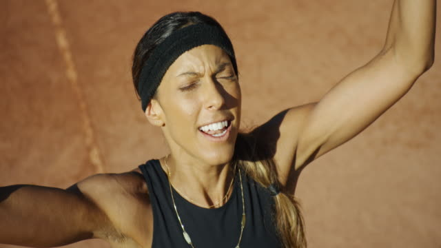Close up slow motion overhead shot of smiling woman celebrating on clay tennis court