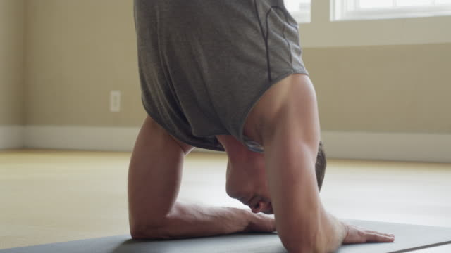 Close up slow motion panning shot of man performing supported headstand / Provo, Utah, United States