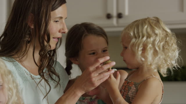close up slow motion panning shot of mother and daughters baking cookies / orem, utah, united states - orem utah stock videos & royalty-free footage