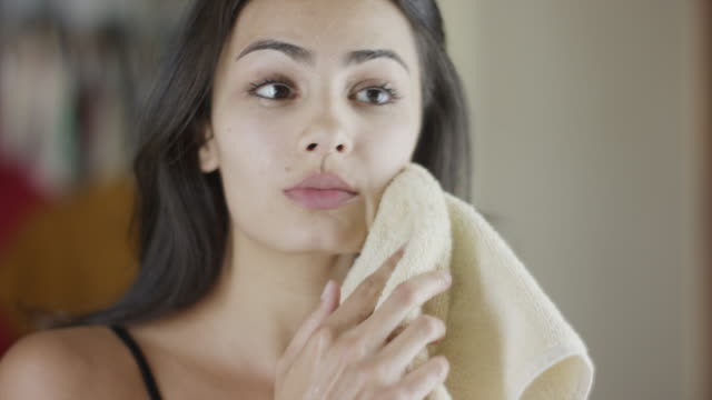 Close up slow motion panning shot of woman drying face with towel / Cedar Hills, Utah, United States