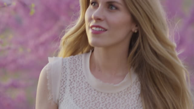 Close up slow motion panning shot of woman smelling flowers in park / Cedar Hills, Utah, United States