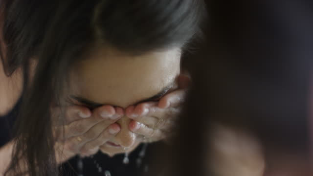 vídeos de stock e filmes b-roll de close up slow motion reflection of woman washing face in mirror / cedar hills, utah, united states - lava