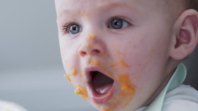 a close up slow motion shot of a face of a 6 month old caucasian baby eating messy food - 6 11 månader bildbanksvideor och videomaterial från bakom kulisserna