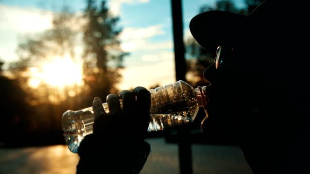 slow-motion-aufnahme eine weibliche silhouette trinkwasser aus einer plastikflasche hautnah - trinken stock-videos und b-roll-filmmaterial