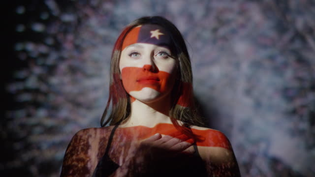 Close up slow motion shot of American flag projections on face of woman / Cedar Hills, Utah, United States