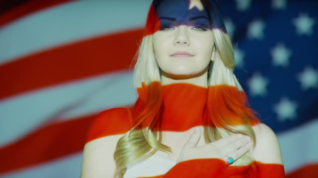 close up slow motion shot of american flag projections on woman / cedar hills, utah, united states - amerikanischer treueschwur stock-videos und b-roll-filmmaterial