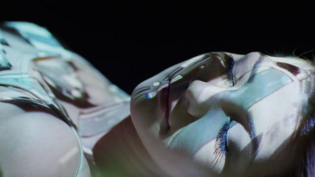 Close up slow motion shot of car projections on woman's face / Cedar Hills, Utah, United States