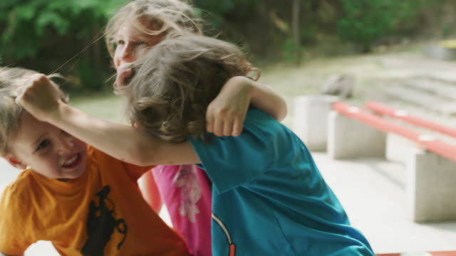 Close up slow motion shot of children hugging then fighting / Plovdiv, Bulgaria