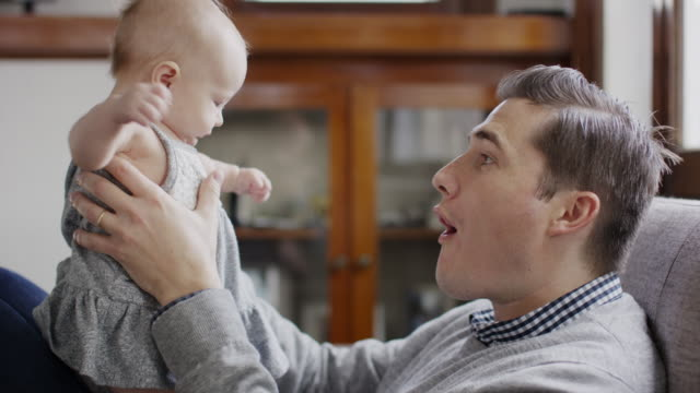close up slow motion shot of father kissing baby daughter on lap / provo, utah, united states - provo stock videos & royalty-free footage