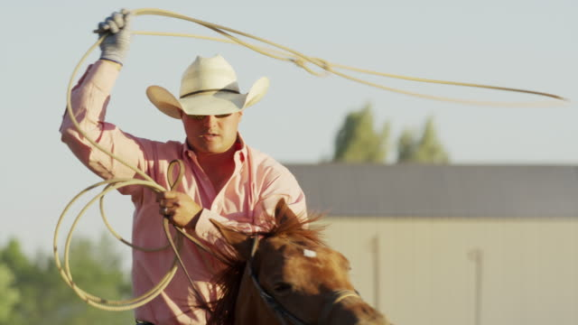 close up slow motion shot of man riding horse spinning lasso / lehi, utah, united states - lehi stock videos & royalty-free footage