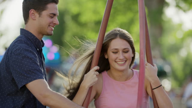Close up slow motion shot of man spinning woman on swing / Pleasant Grove, Utah, United States