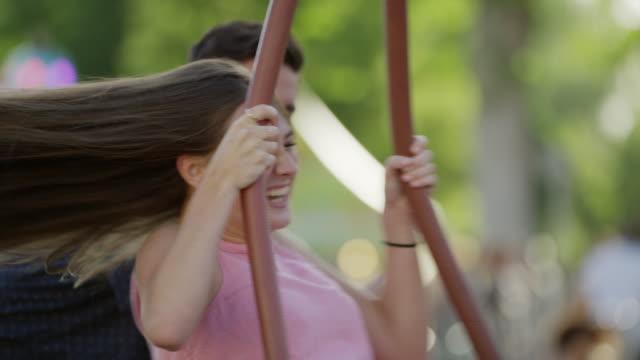 close up slow motion shot of man spinning woman on tire swing / pleasant grove, utah, united states - heterosexuella par bildbanksvideor och videomaterial från bakom kulisserna