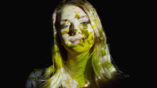 'Close up slow motion shot of multimedia projections on smiling woman‰Ûªs face / Cedar Hills, Utah, United States'