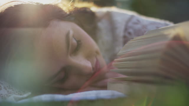 Close up slow motion shot of woman napping in park / Cedar Hills, Utah, United States