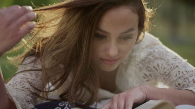 Close up slow motion shot of woman reading book in grass / Cedar Hills, Utah, United States
