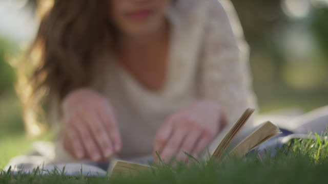 close up slow motion shot of woman reading book in grass / cedar hills, utah, united states - auf dem bauch liegen stock-videos und b-roll-filmmaterial
