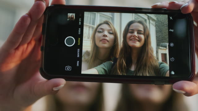 Close up slow motion shot of women posing for cell phone selfie / Plovdiv, Bulgaria