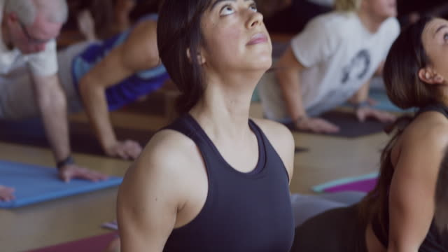 close up slow motion shot of yoga class changing poses / provo, utah, united states - chin ups stock videos and b-roll footage