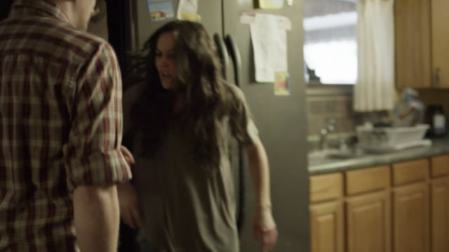 vídeos de stock e filmes b-roll de close up slow motion tracking shot of angry man chasing woman in kitchen / springville, utah, united states - criminoso