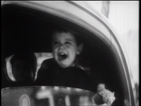 B/W 1939 close up small boy sitting in car crying / documentary