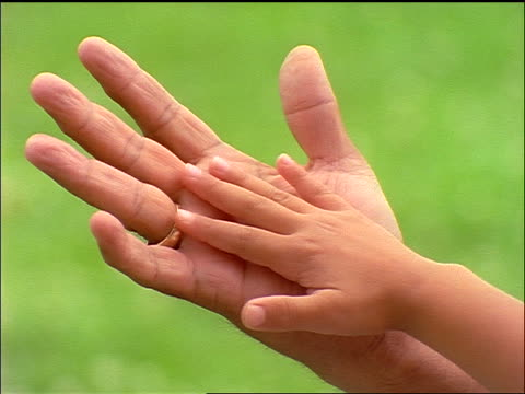 close up small child's hand moving on palm of senior woman outdoors