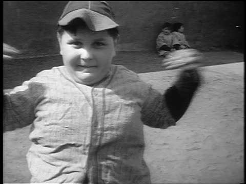 vídeos de stock e filmes b-roll de b/w 1941 close up small fat boy in baseball uniform doing exercises outdoors / nyc / newsreel - gordo