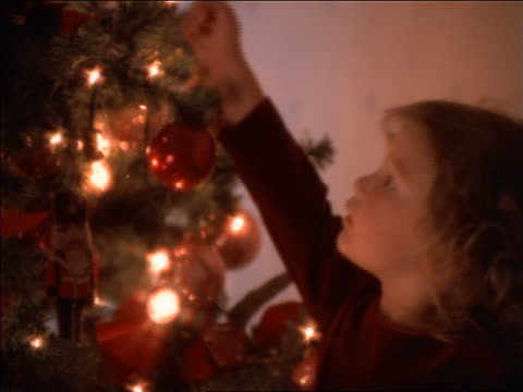 stockvideo's en b-roll-footage met close up small girl putting ornament on christmas tree - kerstboom versieren