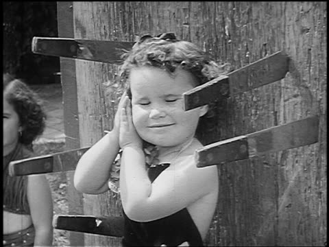 B/W 1955 close up small girl standing against board as knives are thrown around her / gestures to camera