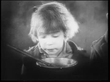b/w 1922 close up small orphan boy (jackie coogan) licking bowl with finger / feature - licking stock videos & royalty-free footage