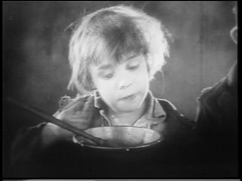 b/w 1922 close up small orphan boy (jackie coogan) licking bowl with finger / feature - orphan stock videos & royalty-free footage