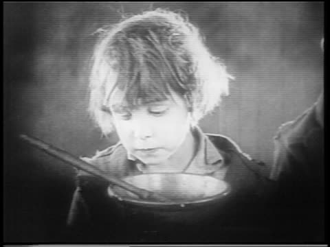 vidéos et rushes de b/w 1922 close up small orphan boy (jackie coogan) licking bowl with finger / feature - orphelin