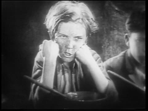 vidéos et rushes de b/w 1922 close up small orphan boy with freckles looking menacing + making fist / feature - orphelin