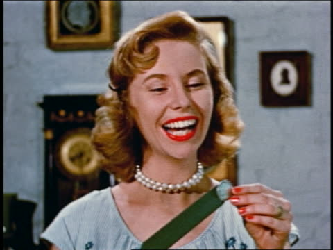 1950 close up smiling blonde woman pulling quarter from vacuum cleaner hose - vacuum cleaner stock videos & royalty-free footage