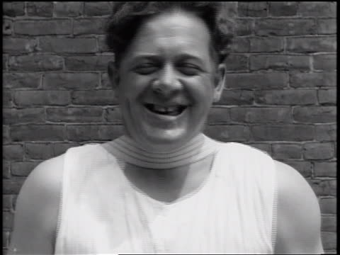 vidéos et rushes de b/w 1935 close up smiling face of policemen with vibrating strap on neck / newsreel - shaking